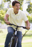 Man outdoors riding bike smiling Royalty Free Stock Photos