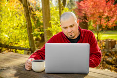 Man outdoors Smiling at Laptop Holding Coffee royalty free stock photos