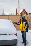 A man outside cleaning off the car after snow flurry Royalty Free Stock Photo