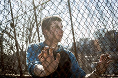 Man outside close to a fence without feeling Stock Image