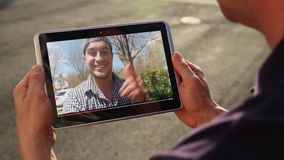 Man watches a viral video vlogger outside on tablet pc. A man outside his home watches a popular vlogger playing on his tablet PC stock video