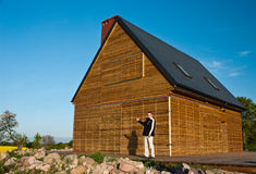 Man outside wooden home Stock Photo