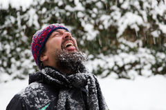 Man with outstretched tongue is catching snowflakes Royalty Free Stock Photography