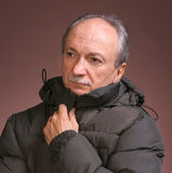 Man in outwear. Close-up portrait of a senior man in winter clothing on a brown background royalty free stock photo