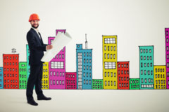 Man over drawing cityscape. Smiley man in orange hardhat with blueprint over many-coloured drawing cityscape Royalty Free Stock Photography