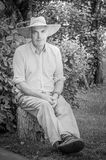 Man over 50 sitting in his garden with summer hat royalty free stock photo