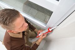Man In Overall Applying Silicone Sealant Stock Photography