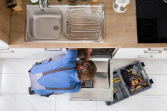 Man In Overall Repairing Dishwasher Royalty Free Stock Photo