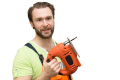 Man in overalls with a jigsaw Royalty Free Stock Photos
