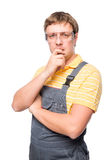 A man in overalls and protective glasses thinking Stock Photo