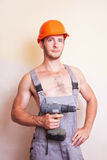 Man in overalls with a screwdriver Stock Photo