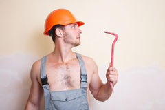 Man in overalls with a tool for dismantling Stock Image