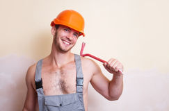 Man in overalls with a tool for dismantling. A man in overalls and helmet with a tool for dismantling Royalty Free Stock Photography