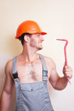 Man in overalls with a tool for dismantling. A man in overalls and helmet with a tool for dismantling Stock Photography