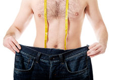 Man with oversized jeans and measure tape. Stock Photo