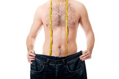 Man with oversized jeans and measure tape. Stock Photos