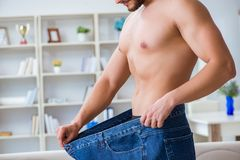 The man in oversized pants in weight loss concept Stock Photos