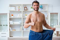 The man in oversized pants in weight loss concept. Man in oversized pants in weight loss concept stock image
