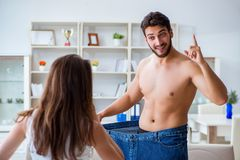 Man in oversized pants in weight loss concept with girlfriend wi Royalty Free Stock Photos