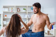 Man in oversized pants in weight loss concept with girlfriend wi Stock Images