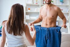 Man in oversized pants in weight loss concept with girlfriend wi Royalty Free Stock Image
