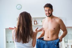 Man in oversized pants in weight loss concept with girlfriend wi Royalty Free Stock Photo