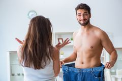 Man in oversized pants in weight loss concept with girlfriend wi Stock Photography