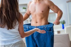 Man in oversized pants in weight loss concept with girlfriend wi Royalty Free Stock Images