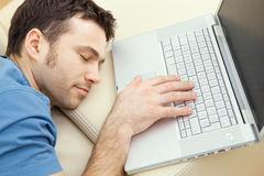 Man overslept by laptop. Man overslept by the keyboard of a laptop computer. eyes closed, high-angle view Royalty Free Stock Images