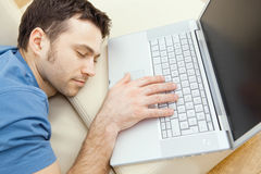 Man overslept by laptop Stock Images