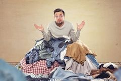 Man overstrained with housekeeping. A man is covered by a heap of laundry. He has got a clueless expression and his palms are turned upwards Stock Photography