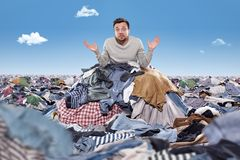 Man overstrained with housekeeping. A man stuck inside a pile of clothing. The landscape around him is covered in clothing, too Royalty Free Stock Photo