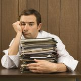 Man with overwhelmed face. Mid-adult Caucasian male with overwhelmed face holding lots of paperwork Royalty Free Stock Photography