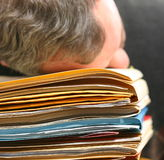 Man overwhelmed with office work. Man in an office situation overwhelmed by paperwork Royalty Free Stock Images