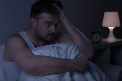Man overwhelmed with stress. Horizontal photo of a man too stressed to fall asleep Stock Photography