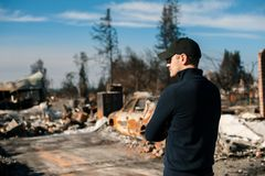 Man owner checking ruins after fire disaster. Man owner checking burned and ruined house and yard after fire, consequences of fire disaster accident. Ruins royalty free stock photos