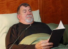 Man with Oxygen Cannula Reading in Bed. A man with an oxygen cannula in his nose reads in bed Royalty Free Stock Photo