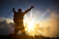 Man på överkanten av hållande ögonen på soluppgång för berg arkivbilder