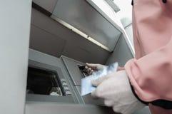 Man på ATM-maskinen med gömstället av krediterings- och debiteringkort royaltyfria bilder