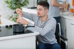 Man på att laga mat för rullstol royaltyfria bilder