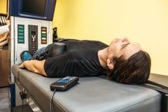Man på behandlingåterställningssjukgymnastik av den mänskliga ryggen, genom att sträcka med special medicinsk utrustning i klinik royaltyfria foton