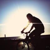 Man på cykelridning på en kustlinje Arkivbild