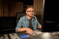 Man på den blandande konsolen i musikinspelningstudio Arkivfoto