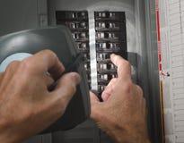 Man på den bostadspanelen för strömkretssäkerhetsbrytare Arkivfoton