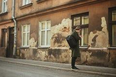 Man på den gamla gatan som röker cigaretter, i ett långt lag Mannen hjälper en cigarett i staden En man som från gamla filmer royaltyfri fotografi