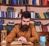 Man på den koncentrerade framsidaläseboken som studerar, bokhyllor på bakgrund Självutbildningsbegrepp Lärare eller student Royaltyfri Bild