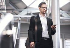Man på den smarta telefonen - ung affärsman i flygplats Stiliga män i glasögon som bär dräkten, klår upp inomhus Fotografering för Bildbyråer