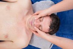 Man på en ansikts- massage för massagetabellhäleri Royaltyfri Foto