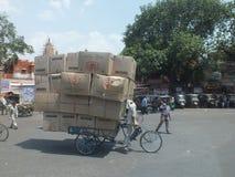 Man på en cykel med askar Royaltyfri Foto