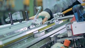 Man på en fabrik som drar åt skruvarna genom att använda den industriella elektriska skruvmejseln arkivfilmer